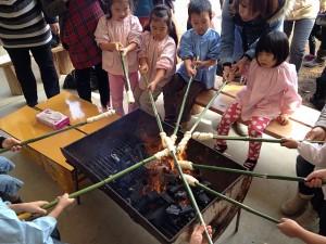 パンを竹に巻いて炭火で焼いています